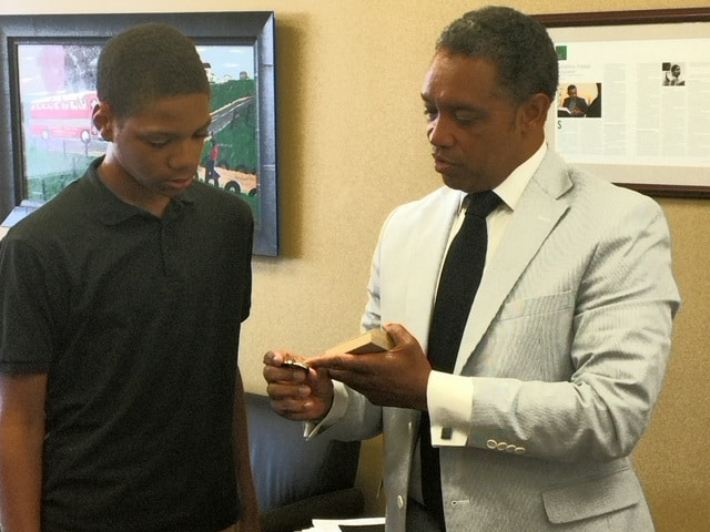 D.C. Attorney General Karl Racine awards Warren King, an eighth-grader at Johnson Middle School with a Right Direction Award.